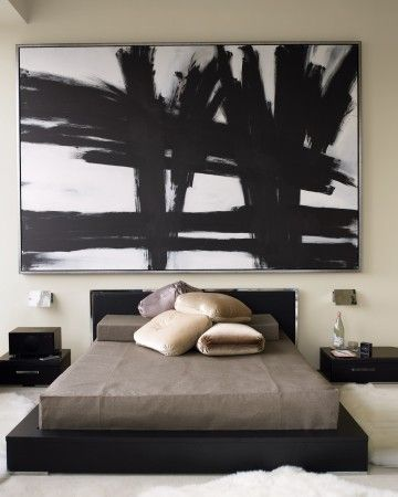 """""""I wanted the bed to look like a bento box,"""" Kevin Sharkey says. A low platform bed frame stained black alongside marble-topped tables achieves the effect. An oversize graphic painting against beige walls helps furniture to feel grounded in the soaring room.See More from Kevin Sharkey's Apartment Tour"""
