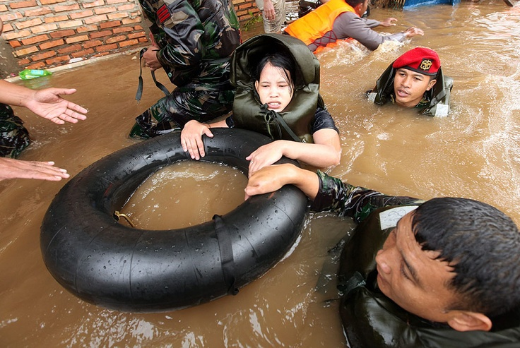 A woman is evacuated from her home by officials during flooding on Indonesia's capital on January 18, 2013   © Adi Weda   EPA