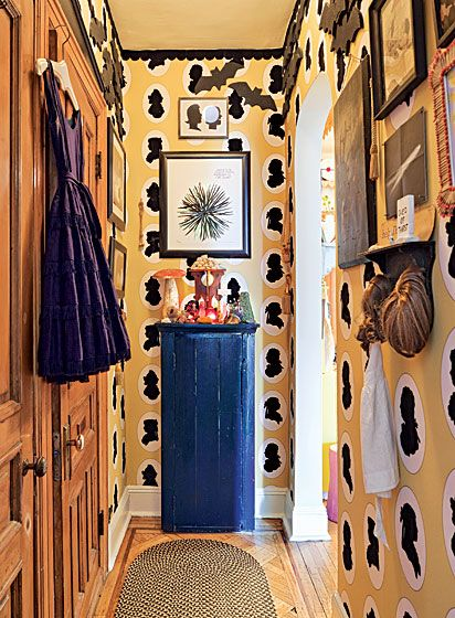 The apartment of Amy Sedaris: The hallway leading to the bedroom is papered in Osborne & Little flocked wallpaper. The wood bats were made by artist Brock Shorno, whom Sedaris commissioned after finding two similar-looking bats at a flea market.