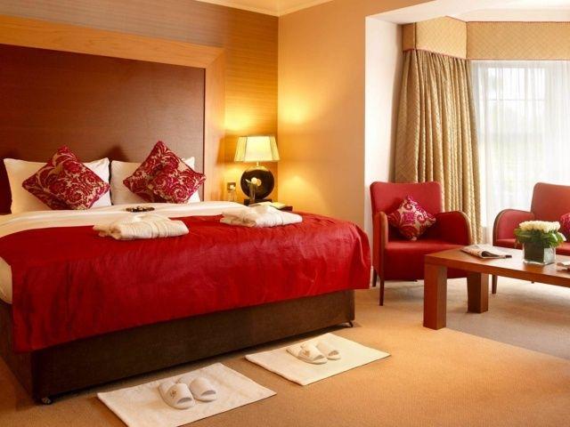 chambre lit fauteuil rouge coussins rideaux beige lampe