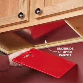 Clever! Put magnets on a cutting board, attach a metal plate to the underside of the cabinets. Viola!