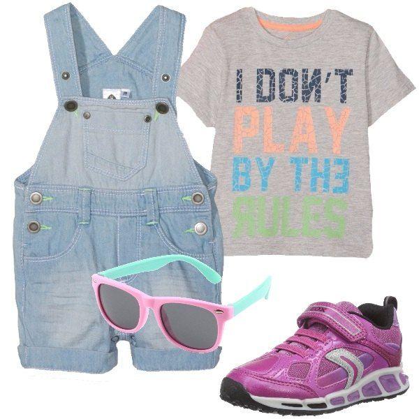Un outfit vivace per una bimba composto da: salopette in denim, t-shirt con stampa colorata, occhiali da sole gommati e flessibili e scarpe da ginnastica fucsia.