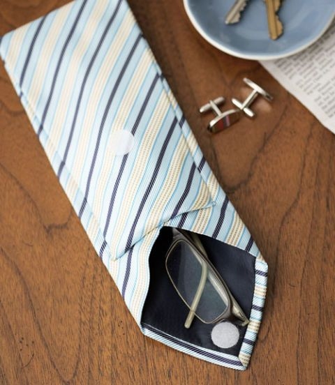 Transform a traditional necktie into a nifty eyeglass case. (A fun gift idea for Father's Day!) Step 1: Lay a tie front side down. Measure and mark 17 inches in from the pointed tip, then cut the tie widthwise. Discard the narrow end of the tie. Step 2: Using a seam ripper, open the seam along the back of the tie at least six inches, to create a pouch for the glasses. Step 3: Measure eight inches in from the cut end and mark. Fold the tie at the mark toward the pointed tip; tuck under 1/2…
