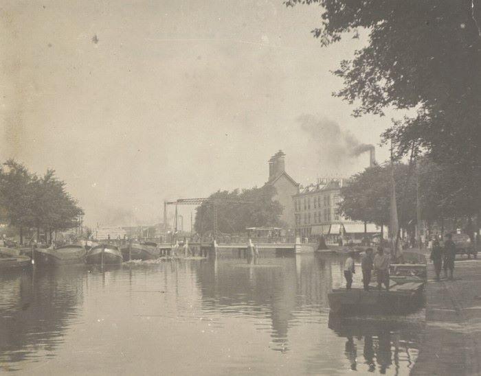 Gezicht op de Heineken brouwerij te Rotterdam, gezien over het water van de Rotte. Op de hoek bij de brug Café Hollandia, daarachter met de schoorstenen de eesterij ofwel mouterij. De hier nog zichtbare Noorderophaalbrug werd in 1911 verplaatst. (Foto uit 1906)