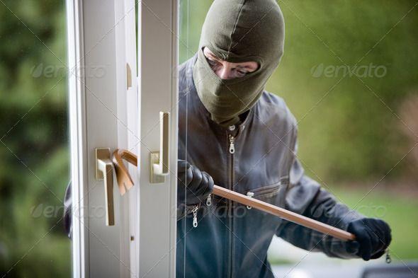 A burglar breaking in the window of a house. http://photodune.net/item/burglar-at-a-window/1800189