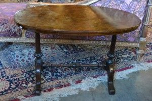 Africa then & now - Provenance Auction House: A Victorian Walnut and Mahogany Loo Table. Oval top with walnut qaurter verneering above carved fluted upright on splayed legs with central carved support. 1050 x 585 x 700mm.