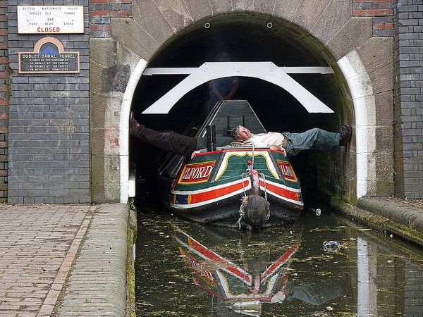 """Legging"" a narrowboat through the Dudley Canal Tunnel, West Midlands, England."