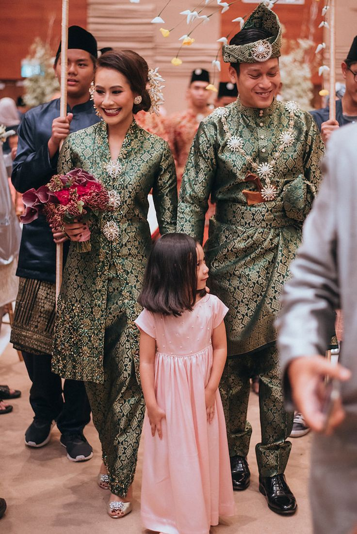 Bride and groom dressed in matching traditional green wedding costumes from Ishq by Nora Zee marching in a traditional Malay bridal procession led by their flower girl dressed in pink // Two worlds became one on Razif and Sarah's big day as the couple tied the knot in a combined celebration that honoured both Arabic and Malay cultures. The couple's Singapore wedding was shot by Hafizudin Hamdan Photography and held at The Grassroots' Club in the presence of nearly 1700 people.