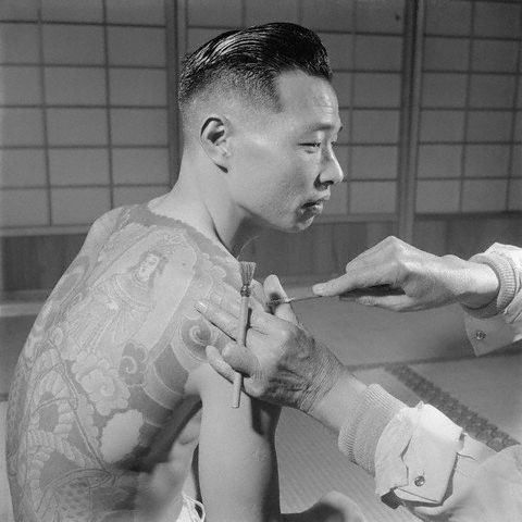 1946, Tokyo, Japan ~ A Japanese tattoo artist (ex Yakusa himself see his left hand) works on the shoulder of a Yakuza gang member. ~ Image by © Horace Bristol