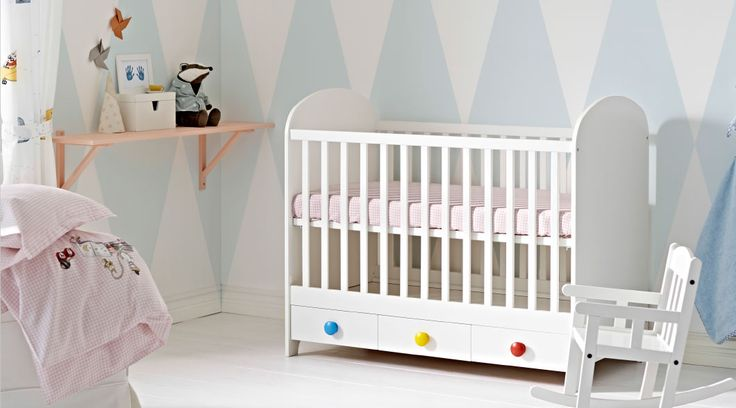 A nursery with a white baby crib with three floor drawers