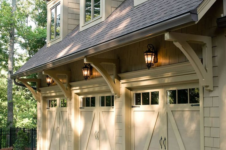 Carriage garage doors with glass, support brackets, lanterns above