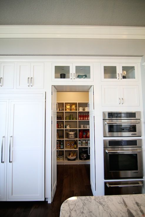 Fantastic kitchen features concealed pantry hidden behind pantry cabinet doors flanked by bi-fold cabinet doors to the left and microwave oven stacked over oven and warming drawer to the right.