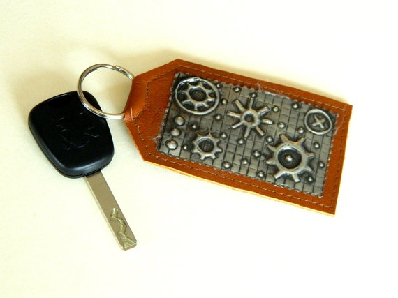 "Add a touch of steampunk to your keys! This genuine leather keyring in a tan colour has a pewter repousse steampunk design on the front. Ideal Fathers Day Gift     This leather keyring measures 10cm (4"") (excluding ring) x 6cm ( 2 1/4"") wide."