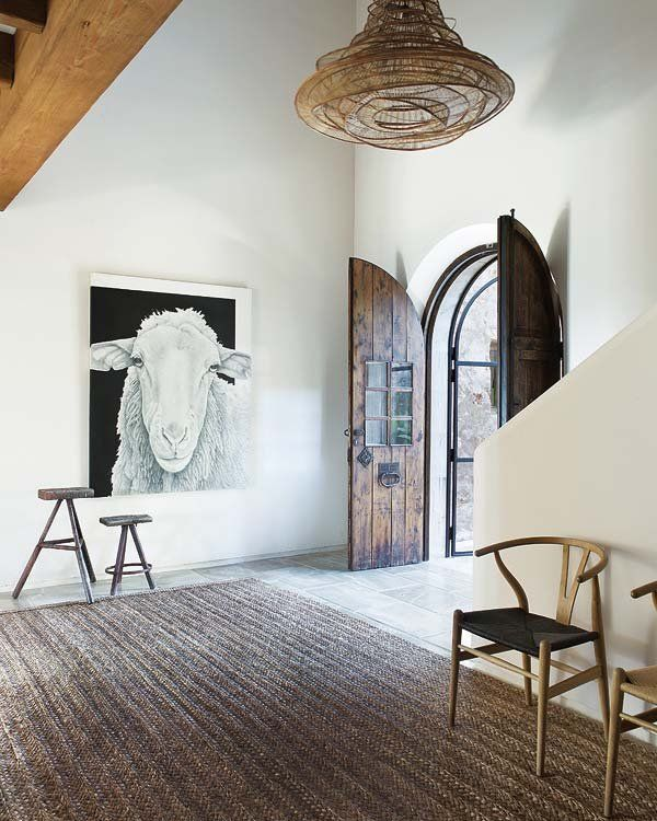 el gran cuadro con la cabeza de una oveja, obra de Castellanos, y la estera que cubre el suelo, adquirida en Rialto Living. La lámpara es de Concha Bay.