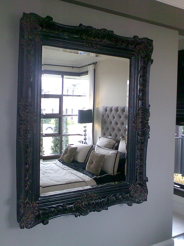 large framed mirror to bedroom wall