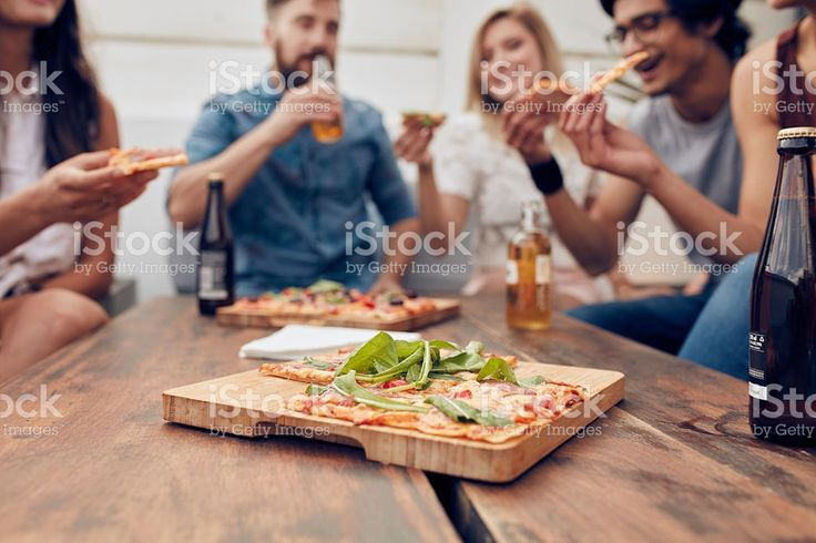 Pizza on table with friends enjoying party royalty-free stock photo