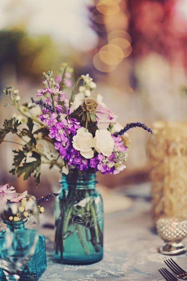 purple and white floral arrangements in blue mason jars