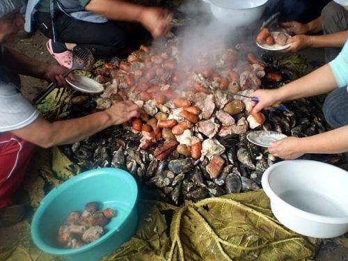 "Curanto.....(from Chiloe, southern Chile. Prepare outdoor, taking the name ""curanto in-hole"", ie it is made into a pit dug in the ground, about five feet deep. The bottom is covered with stones that are heated in a fire. When red-hot coals are removed and you begin to put the ingredients are different types of seafood, meat, potatoes, sausages, sausages, chapaleles, milcaos and covered with large leaves of a plant called pangue or nalca, or failing that, with cabbage leaves)."