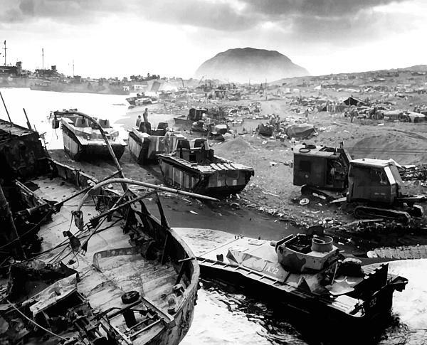 This image shows the devastated wreckage of the beach during The Battle Of Iwo Jima during World War Two. Mount Suribachi can be seen in the background.