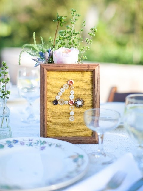 Found frames and buttons. For a rustic look use burlap for the backdrop or fabric remnants you an pick up at a thrift store or your mom's rag bag.
