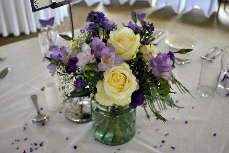 Vintage, country garden centrepiece. Recycled glass jar with mixed hand tied of roses, freesia, lisianthus and gypsophila - from Laurel Weddings