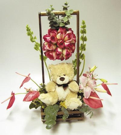 Hermoso arreglo floral con una delicada esfera de rosas, anturios, aompañado de un peluche.