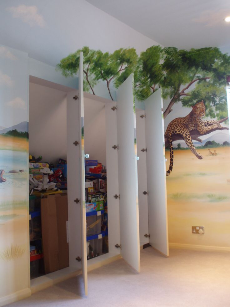 Fitted wardrobes with flat doors painted with trompe-l'œil safari scenes.