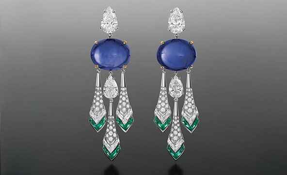 Chandelier earrings set with a pair of velvet blue cabochon sapphires (49.38 cd), suspending pear shaped diamonds and diamond set elongated elements bordered by a line of emeralds. BVLGARI