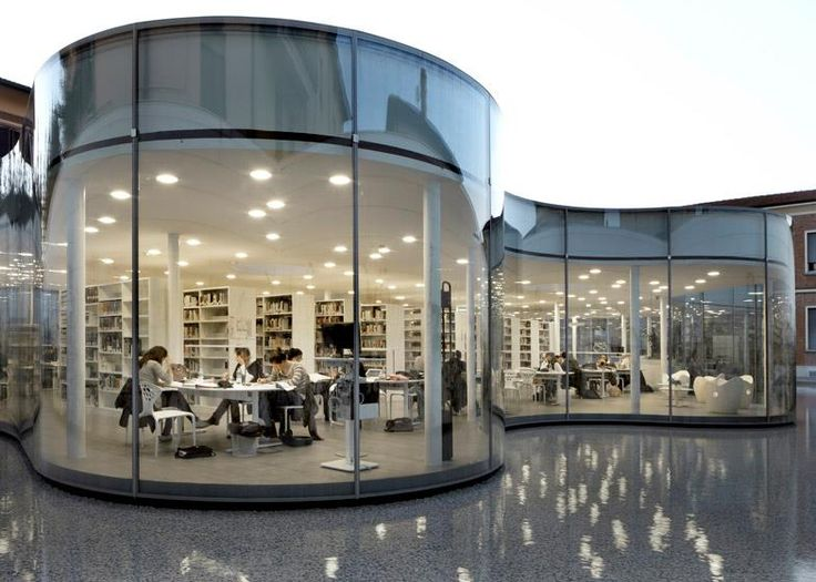 A glazed reading room appears to float over the still waters of a shallow pool at this town library in Maranello, Italy, by Japanese architect Arata Isozaki and Italian architect Andrea Maffei. The curving glass facade wiggles back and forth to form the building's perimeter, while study areas behind the glass offer visitors a view out across the water towards the ivy-covered walls that bound the site.