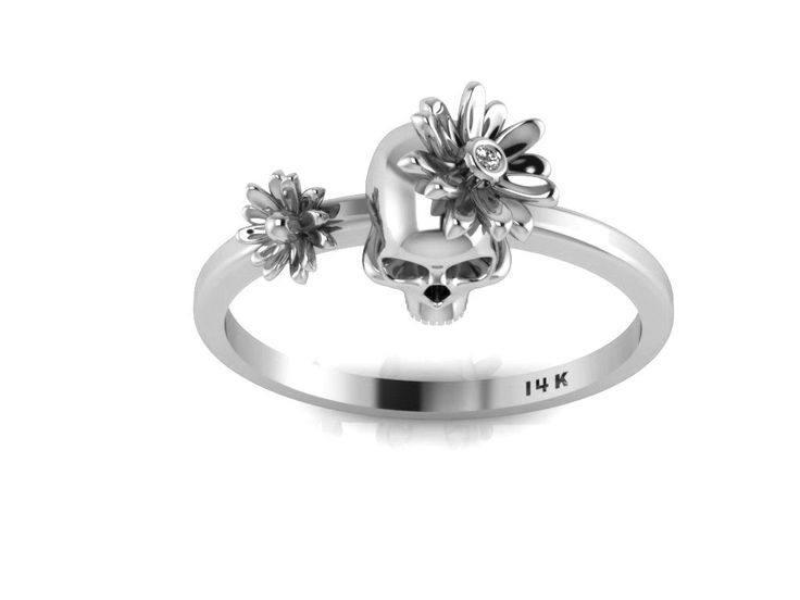 This is our new Skull Ring! Here the Dark and Light come together for this skull ring with flowers. Made in 14k White Gold this ring has two Daisy Flowers and there is a tiny White Diamond set in one