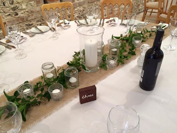 Table decorations- hessian table runner and olive branches. Only a few candles no table numbers.