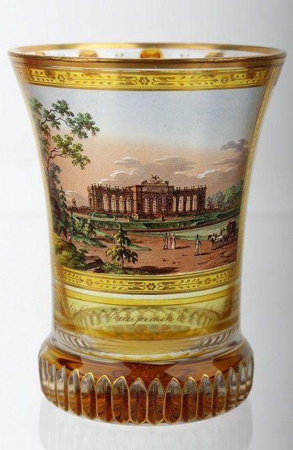 Rakousko, Vídeň, Anton Kothgasser (1769-1851), signováno AK, okolo roku 1825, zvoncovitá číše s vertikálními klínovými řezy na nízké kruhové patce, čiré sklo, broušené, žlutě lazurované, ručně malované transparentními barvami a zlatem, na čelní straně veduta s motivem Schönbrunnu a žlutě lazurovaný pás se zlatým nápisem Vue de la Gloiette au Jardin de Schönbrunn, zlacené hrdlo s malovanými ornamenty, na hrdle jedno místo restaurováno (stará oprava), rozměry 12 x 9,2 x 9,2 cm.