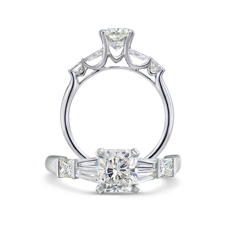 This unique design is an outstanding radiant cut diamond of 1.03ct with F colour VS2 clarity flanked by diamonds to enhance the beautifully cut centre stone.
