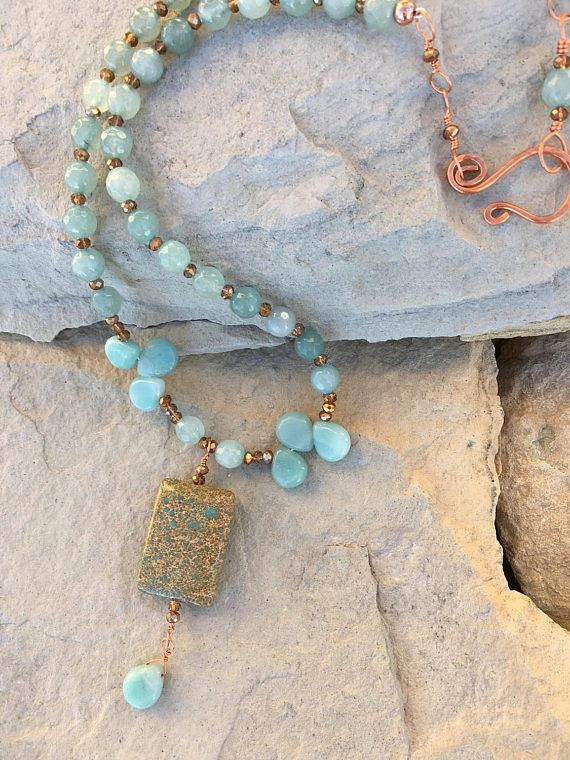 Beautiful cool aqua blue stones are set apart with copper faceted glass beads. Jasper stone with aquamarine briolette dangle. Aquamarine briolette accents on each side ending with handmade copper hammered clasp. This necklace is 17 1/2