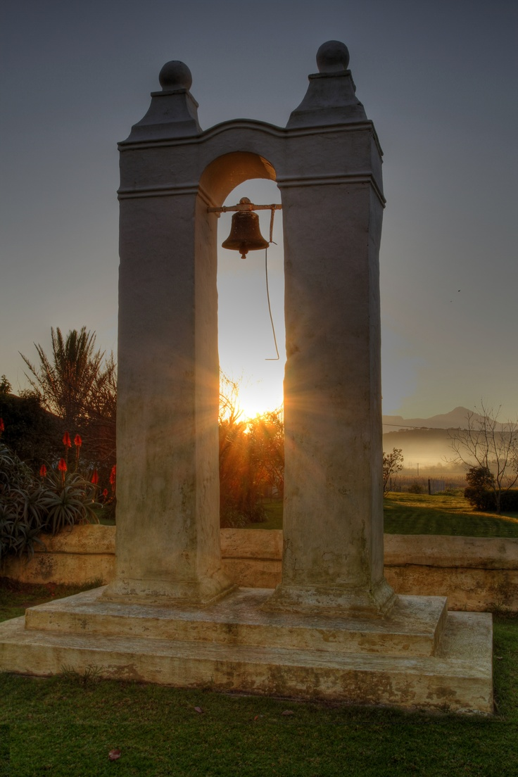 Vergenoegd's Bell Tower with a potent Stellenbosch sunrise in the background amongst the immaculate Helderberg Mountains.