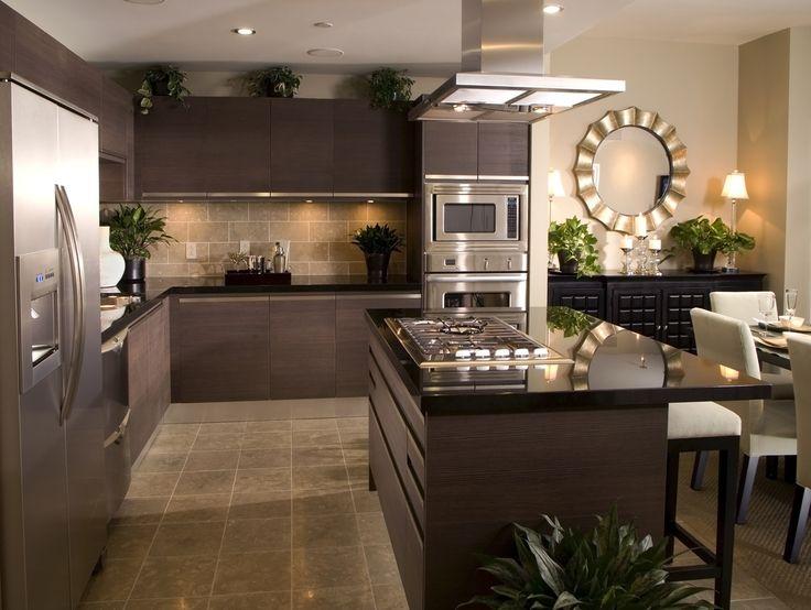Dark kitchen design with dark cabinets, backsplash, counter tops. Island divides open layout from dining area
