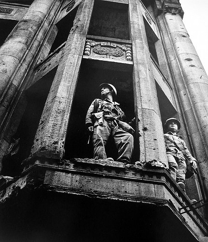 American soldiers look into East Berlin from a war-damaged building in 1961 taken by Don McCullin