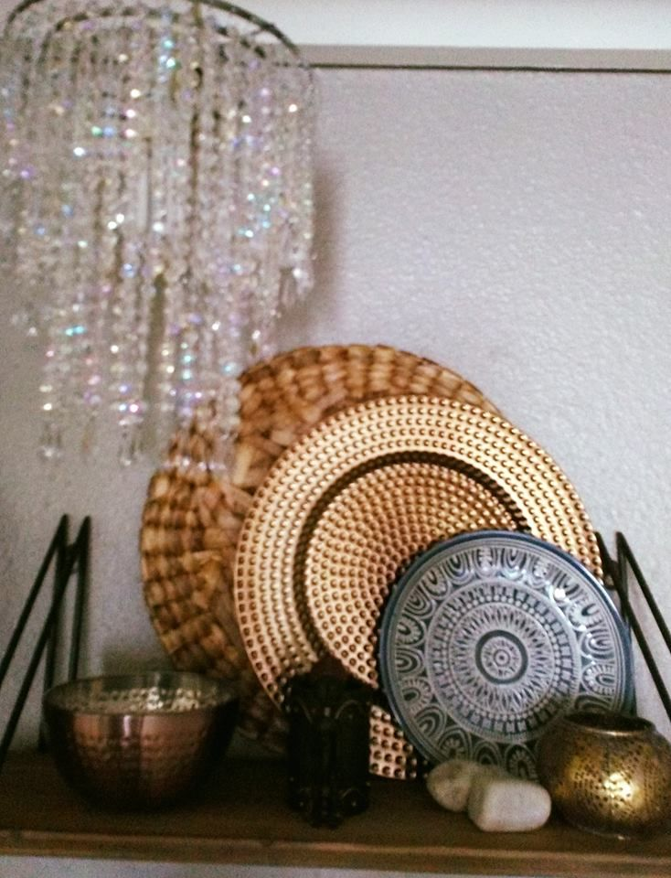 "This shelf adorns a kitchen wall and has been filled with much-loved items to create an almost Moroccan feel.  Items from ""thrift stores"" have been grouped with items from far away places  The chandelier creates an interesting contrast in style.  For assistance in styling  your own home email info@artandspaces.co.za"