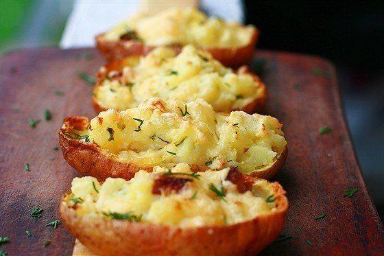 Картофель, запеченный в мундире (4 порции):  Картофель - 4 шт. Чеснок - 4 зубчика Масло сливочное - 100 г Сметана - 2 ст.л. Бекон - 4 шт. Сыр твердый - 200 г Укроп - по вкусу Лук зеленый - по вкусу Соль - по вкусу Перец черный свежемолотый - по вкусу  Приготовление:  1. Разогреть духовку до 200 градусов. Вымыть и обсушить клубни картофеля — кожица должна быть сухой, тогда она подрумянится и станет хрустящей. Каждую картофелину натереть небольшим количеством оливкового масла и солью и…