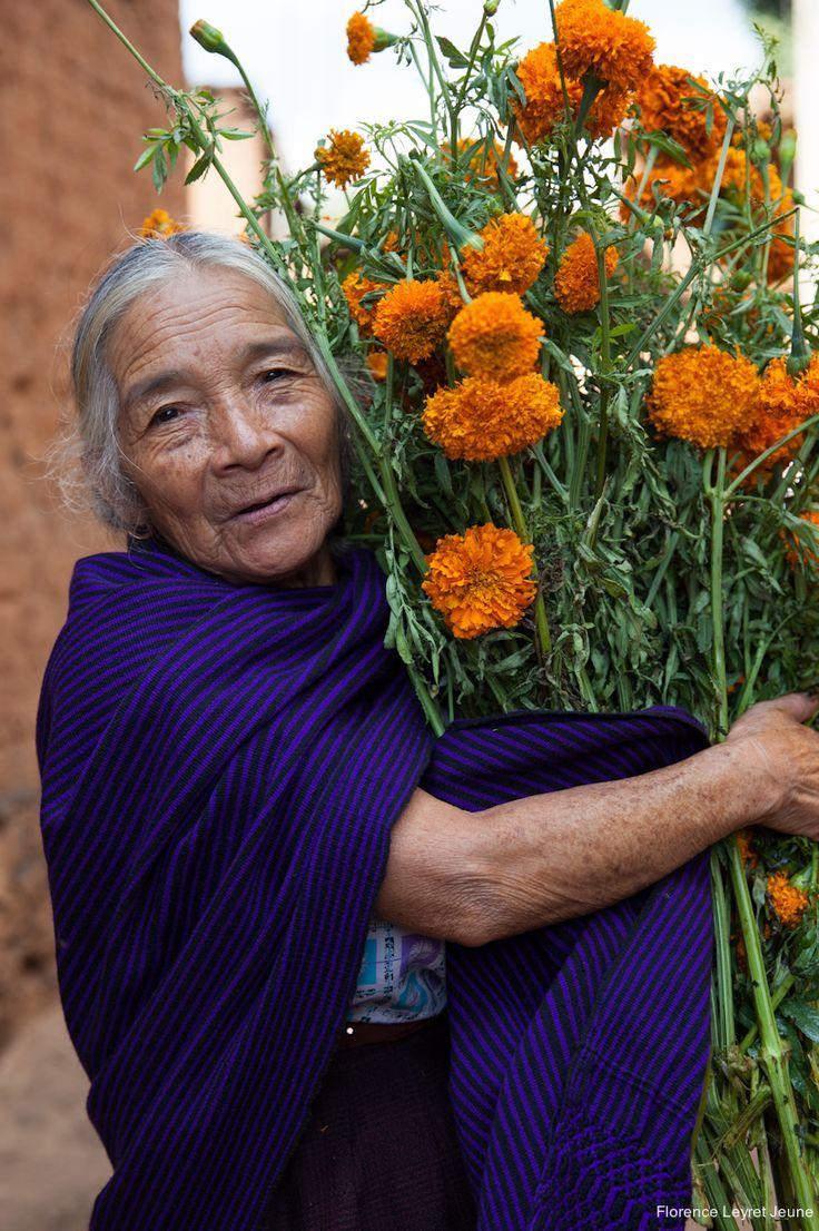 Woman holding flowers in preparation for Dia de los Muertos festivities, Santa Fe de la Laguna, Michoacan, Mexico, 2013, photograph by Florence Leyret Jeune.