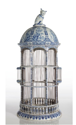 Antique bird cage with cat on top