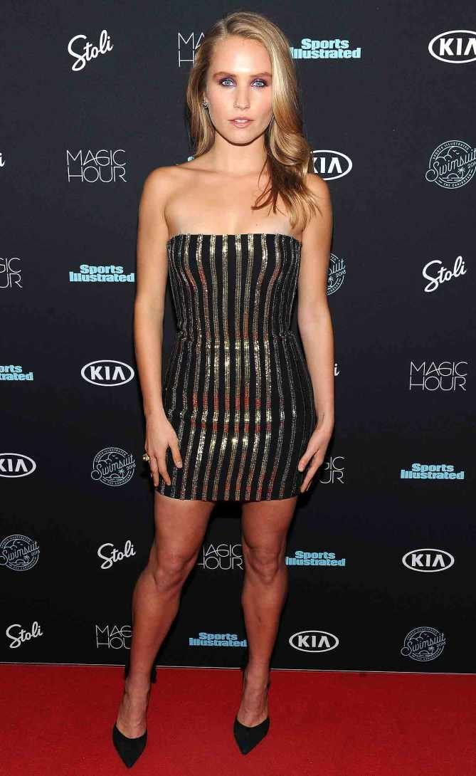 Sailor Brinkley Cook in a strapless black and gold mini dress