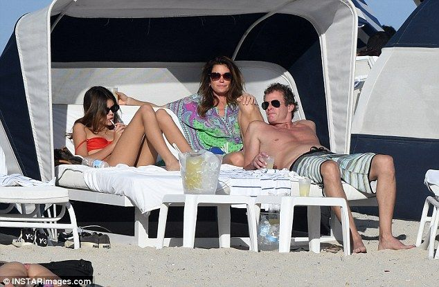 Kicking back: Cindy and Rande Gerber opted to stay dry, marking Christmas Day from their cabana with a few cocktails