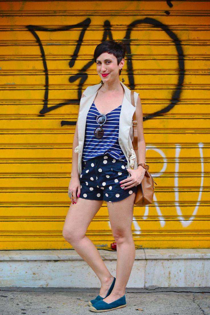 Mistura de estampas e look bom para o verão: short curto azul marinho de bolotas brancas, regata listrada azul e branco, maxi colete em tom cru, alpargatas azuis, bolsa saco caramelo