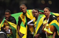 Golden Run-Yohan Blake, Usain Bolt, Nesta Carter and Michael Frater of Jamaica celebrate after winning gold