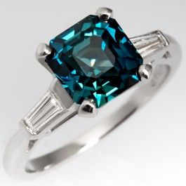This striking blue green sapphire ring is set in a classic platinum mounting with tapered baguette diamond accents. The sapphire is from Madagascar and weights 3.18 carats and has a mixes emerald cut and a beautiful blue-green color. The ring is currently a size 6 and we offer complimentary resizing pitot to shipping.