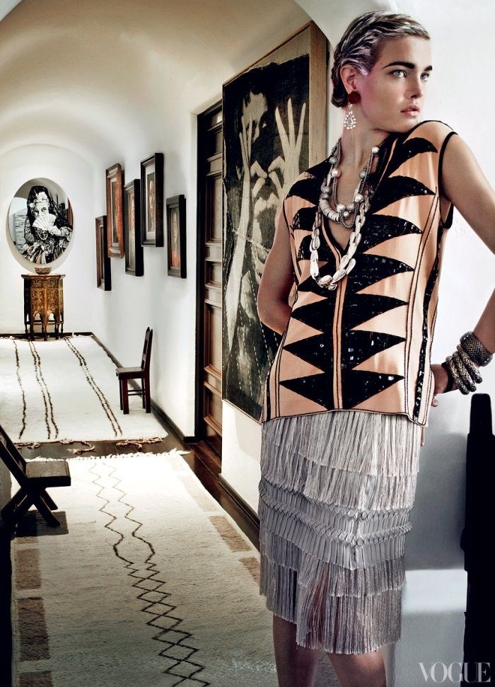 Two long and narrow Moroccan rugs with cream and brown geometric patters balance the baroque heaviness of Hispano-Moresque furniture and complement the modern art in Mario Testino's Los Angeles home. Once again the geometric patterns in the two Moroccan rugs resonate with the patterns in the outfit worn by the model. Image courtesy Vogue Magazine.
