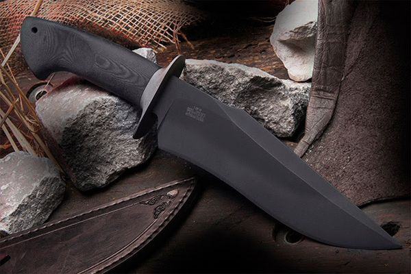 """The Wilson Combat Black Mamba Knife by Scott McGhee is a forged carbon steel fighter with a dangerous curve in every direction. The 7.25"""" 1084 carbon steel is hand forged to shape and then hand ground and convex sharpened to a razor edge. The steel is black phosphate coated for a non-reflective, tactical appearance and hand honed to hair splitting sharpness. A hand contoured stainless guard and slip-resistant micarta handle complete the stealthy package."""