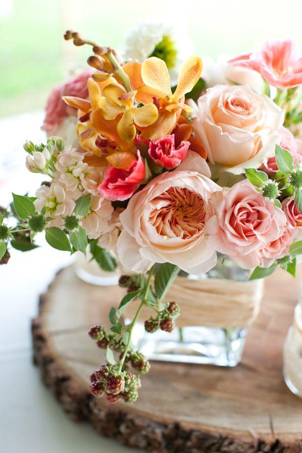 pink, peach and rose wedding florals on a piece of wood http://www.weddingchicks.com/2013/10/30/peach-and-cream-garden-wedding/