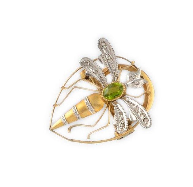 CLIP en or jaune et gris, stylisant une guêpe, sertie sur les ailes de diamants et au centre du thorax, d'un petit péridot ovale. Poids brut: 2,5 g Dimensions: 2,5 cm A diamond and peridot white and yellow… - Osenat - 13/12/2015